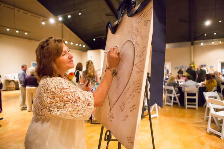 The rustic vibe even extended to their guest book. Friends and family signed a wood-inspired board with well wishes during the reception. A navy ribbon was also draped over the top to match their wedding colors.