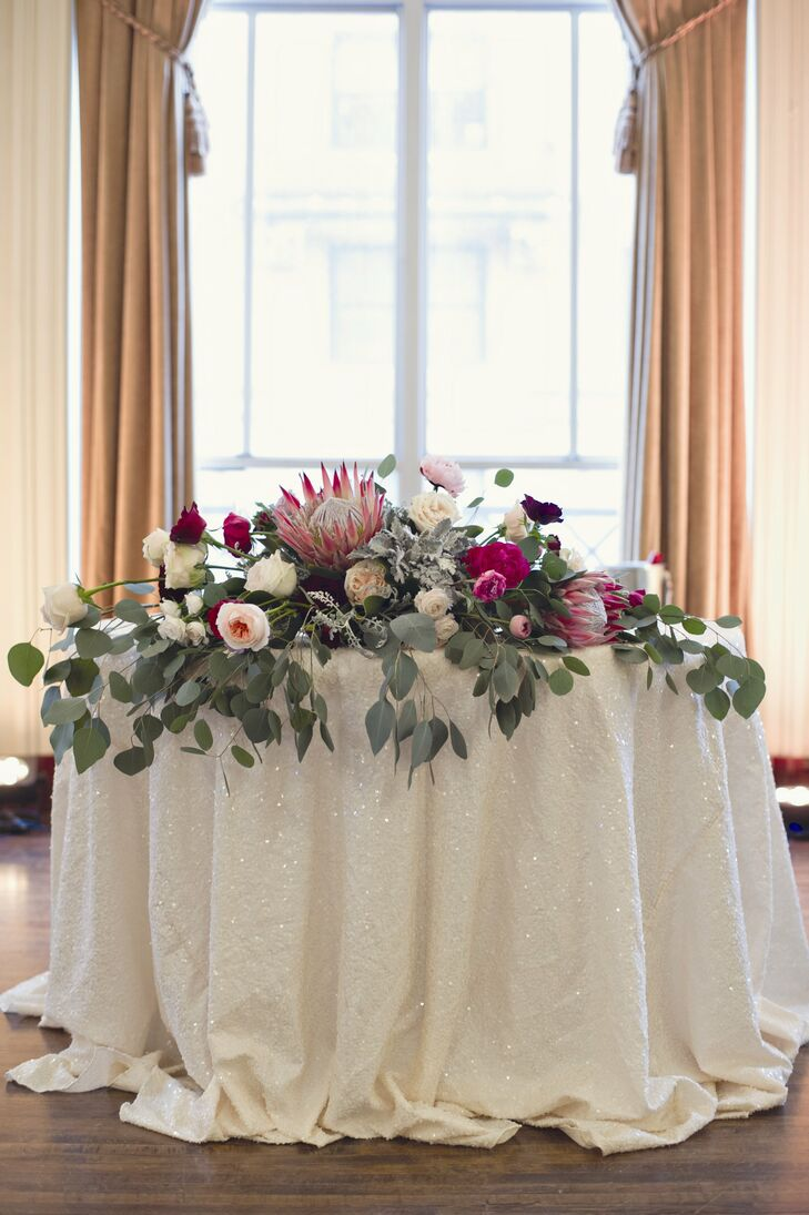 Large proteas, roses and eucalyptus decorated a table at the entrance to the reception.