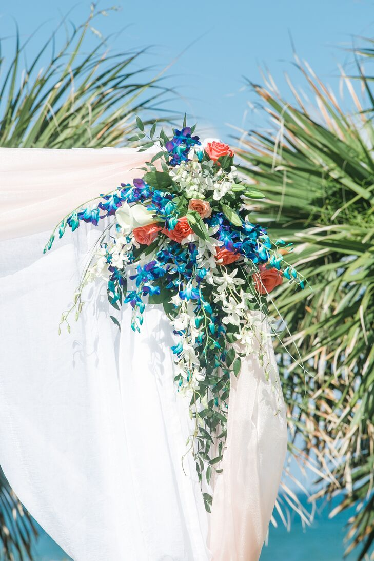 Their wedding arch matched Ashley's bouquet with bunches of colorful blooms. Atmospheres Floral and Decor paired the top of each fabric-draped post with white orchids, coral roses, white calla lilies and eucalyptus. Stems of blue and purple orchids also popped from within the arrangement, creating a dramatic contrast.