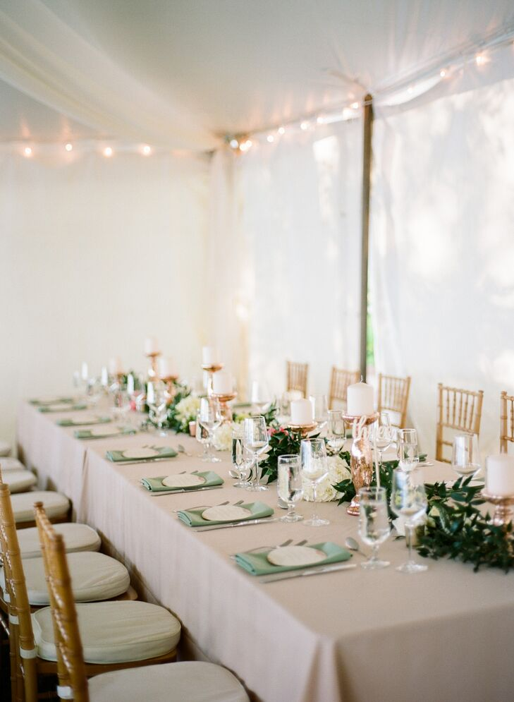 """Our reception was exactly how we envisioned it,"" Jamie says. ""We dressed up our tent with draped fabric and crystal chandeliers, and our centerpieces included a lot of candles to achieve a romantic and intimate ambiance."" Tables were cloaked in soft pink linens and surrounded with elegant gold chiavari chairs."