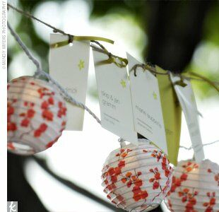 Nikki and Nick strung jute between two trees above the tables at the ceremony and attached ivory and chartreuse escort cards with matching satin ribbon. They added a special touch with small, round, cherry blossom lanterns.
