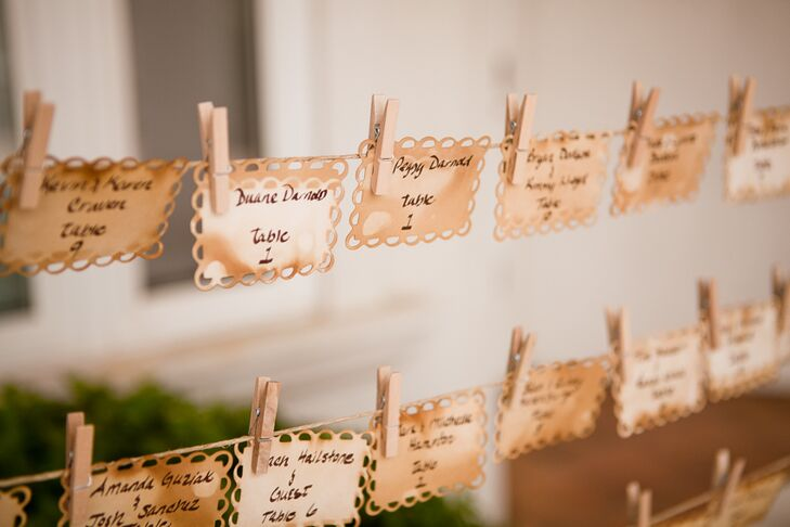 White and beige stained escort cards had the names of guests and their table written on the paper, and were hung with clothespins on lines of wire.