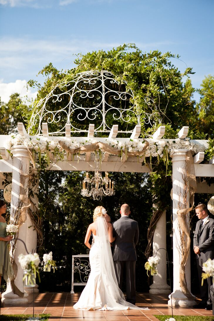 The bride and groom stood next to each other at the ceremonial alter, which had a white wired dome hovering over elegant accents of white wood.