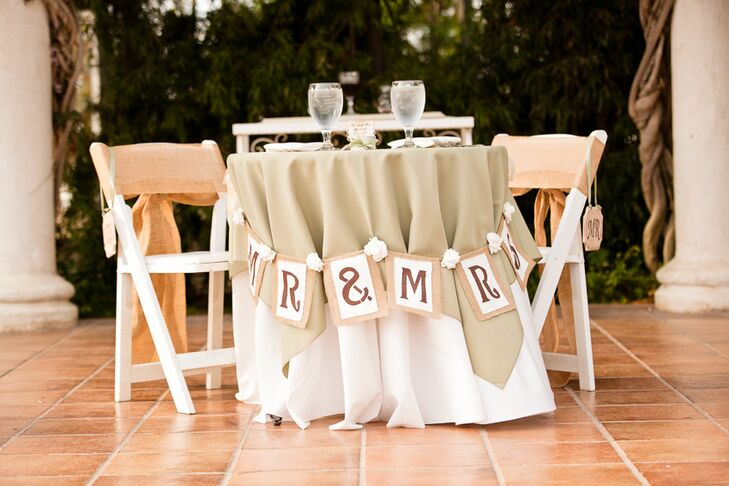 "The sweetheart table at the reception was decorated with beige and white linens, and a ""Mr. & Mrs."" sign hung from the front."