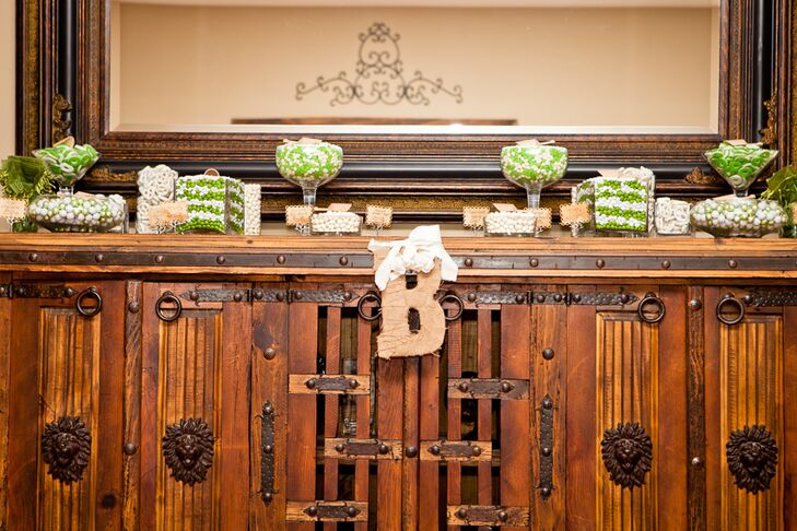 "Glass containers of white and green candy were displayed on a rustic cabinet, with the couple's last name initial ""B"" hanging in front."