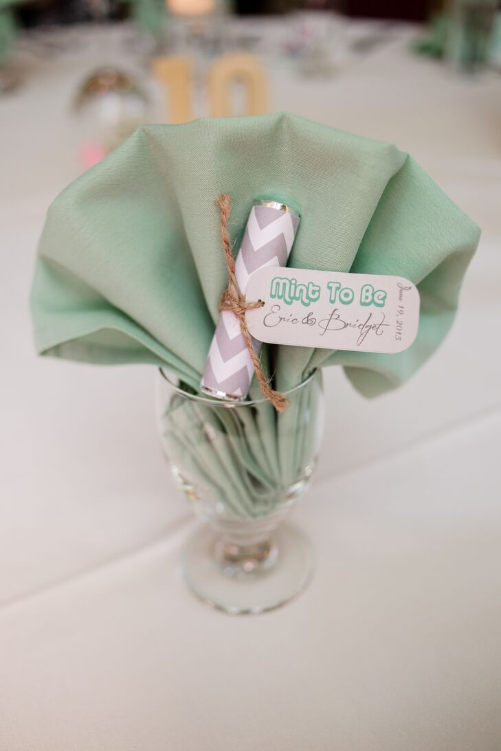 "Mint wedding favors wrapped with gray and white zigzag designs followed the color scheme of the wedding perfectly, with a mint green napkin backdrop! The tags attached to the favors read ""Mint to Be"" along with Bridget's and Eric's names."