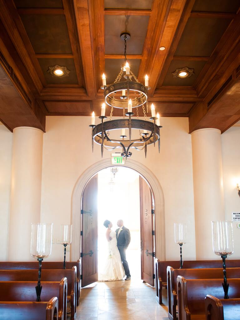 Couple backlit at the doorway of a wedding chapel
