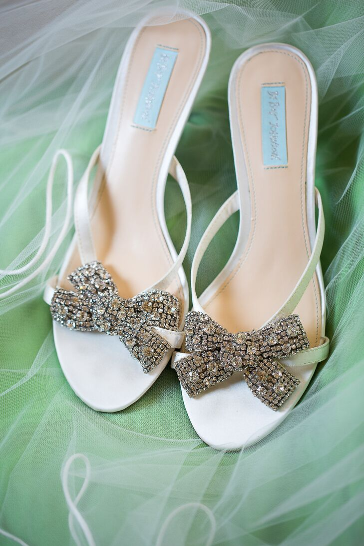 Caitlin wore pale blue sandal heels with rhinestone embellished bows at the toes by Betsy Johnson.