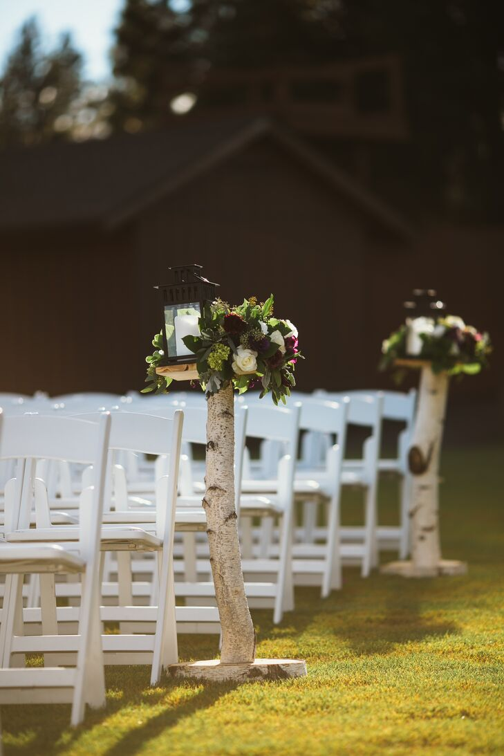 The aisle lined with birch tree trunks had lush flower arrangements of hydrangeas, roses and eucalyptus on top, along with a white candle inside a black lantern.