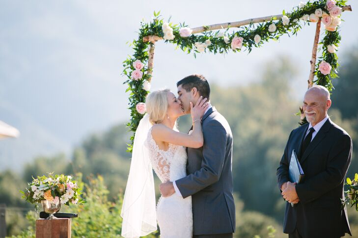Jamie and Jeff shared their first kiss outside at the Holman Ranch venue, with a backdrop of the vineyards and the green rolling hills. The branch wedding arch was positioned behind them, which was garnished by an lush garland of pastel roses and leaves.
