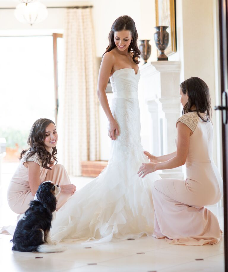 Bridesmaids helping bride in wedding gown
