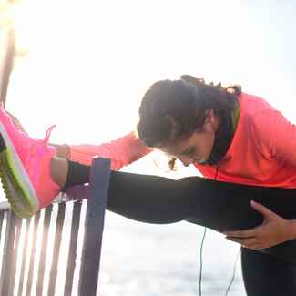 Woman stretching on a banister before working out in pink and black outfit.
