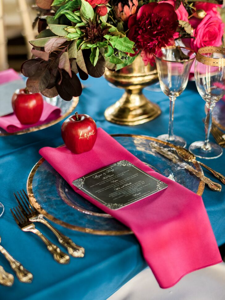 Bright navy and fuchsia jewel tones were used in the table settings alongside gold-rimmed plates and flatware.