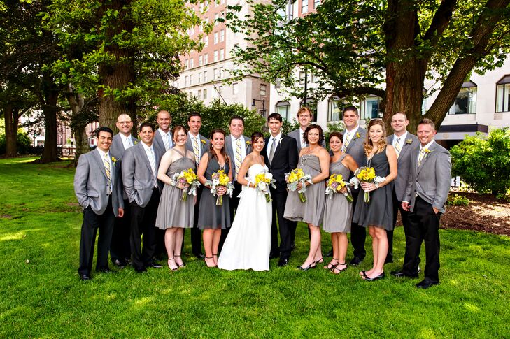 Nicole's bridesmaids wore knee-length, gray dresses in various styles while Nicolas' groomsmen wore classic black pants and casual gray sports coats with yellow-and-gray-striped ties. The yellow bouquets and boutonnieres added pops of color while keeping with the gray and yellow color palette.