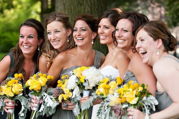 Nicole's bridesmaids wore casual knee-length, gray dresses from J.Crew in various styles. They paired their dresses with yellow bouquets of roses and craspedia, arranged by Joanne Nikitas Creative Floral Design, that added pops of color and kept with the gray and yellow color palette.