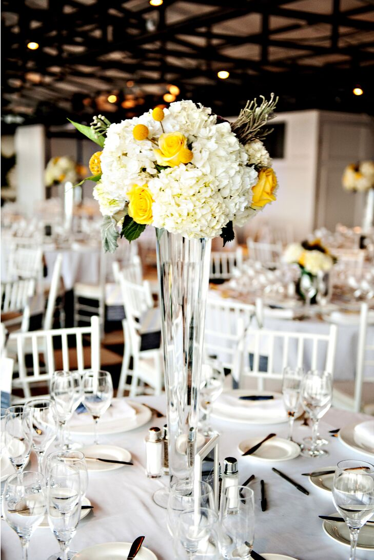 Nicole and Nicolas' contemporary reception at the Taj Boston featured round dining tables dressed in crisp white tablecloths and surrounded by white chiavari chairs. High and low centerpieces of yellow roses and white hydrangeas added elegant dimensions to the otherwise simple decor.