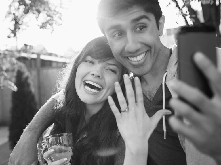 Couple taking selfie with engagement ring