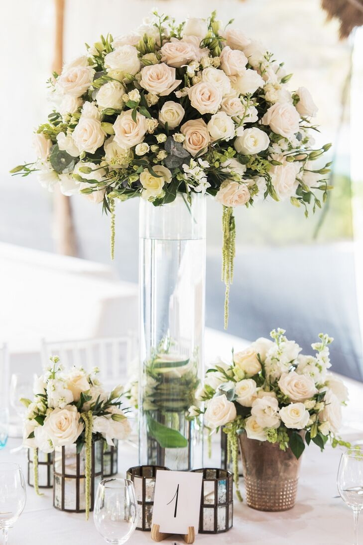 At the reception, which took place at the Rosewood Mayakoba in Riviera Maya, Quintana Roo, Mexico, Vanessa Jaimes Floral Design created high and low centerpieces with white blossoms and subtle greenery.