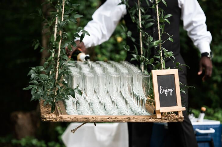At the entrance to the ceremony,  an antique mirror hung from a tree to serve glasses of champagne.