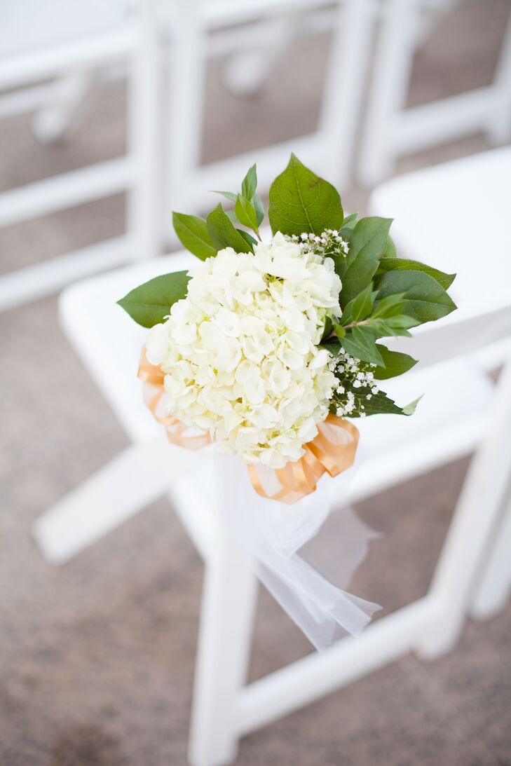 The white folding chairs arranged at the outdoor ceremony had a touch of elegance added to its simple appearance! Bundles of ivory hydrangea mixed with baby's breath and accented with peach ribbon brought color to the simple setup.