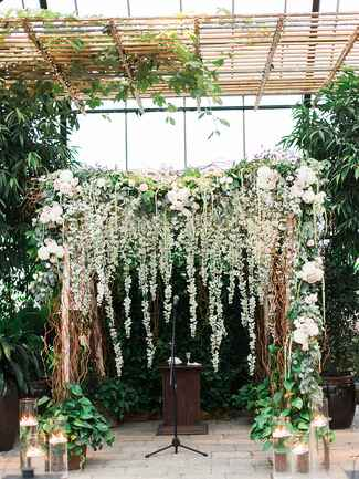 A beautiful birch and willow branch wedding arch draped in flower garlands