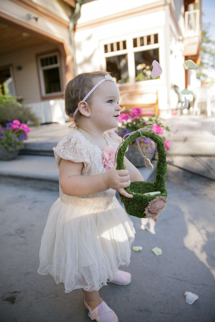 The flower girl looked adorable in her wedding day getup: She wore an ivory-sleeve dress with lace on top and a tulle skirt that flared out, and walked down the aisle in Belfair, Washington, holding a moss-covered basket.