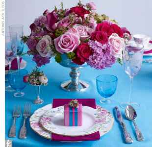 dark pink centerpiece with roses and hydrangeas on a blue tablecloth