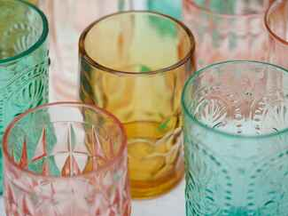 Beautiful colored drinking glasses in teal, yellow and pink on a table