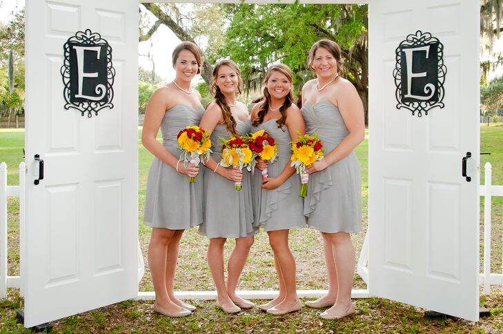 Megan found her wedding-day look and the bridesmaid dresses at the same spot: David's Bridal. Each woman wore a short, light gray dress with a strapless, sweetheart neckline. For an added pop of color, they finished the looks with bright red rose and yellow gerbera daisy bouquets. Megan matched the women with a similar arrangement.