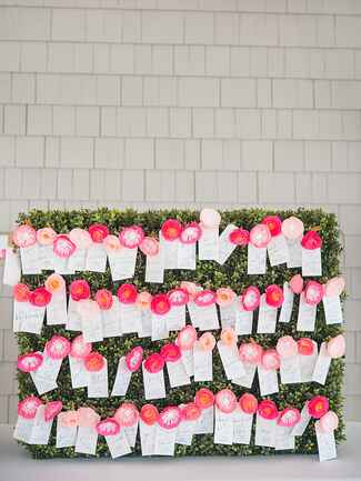 Preppy escort card display with paper flowers and blue calligraphy