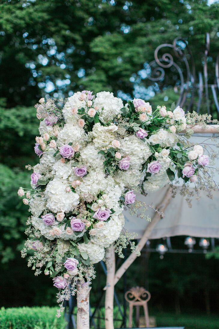"The couple wed under a wooden flower-covered chuppah made by the groom's mother. ""Jesse is one of four siblings, and each corner of the chuppah had a sibling's and spouse's names embroidered,"" Tara says."