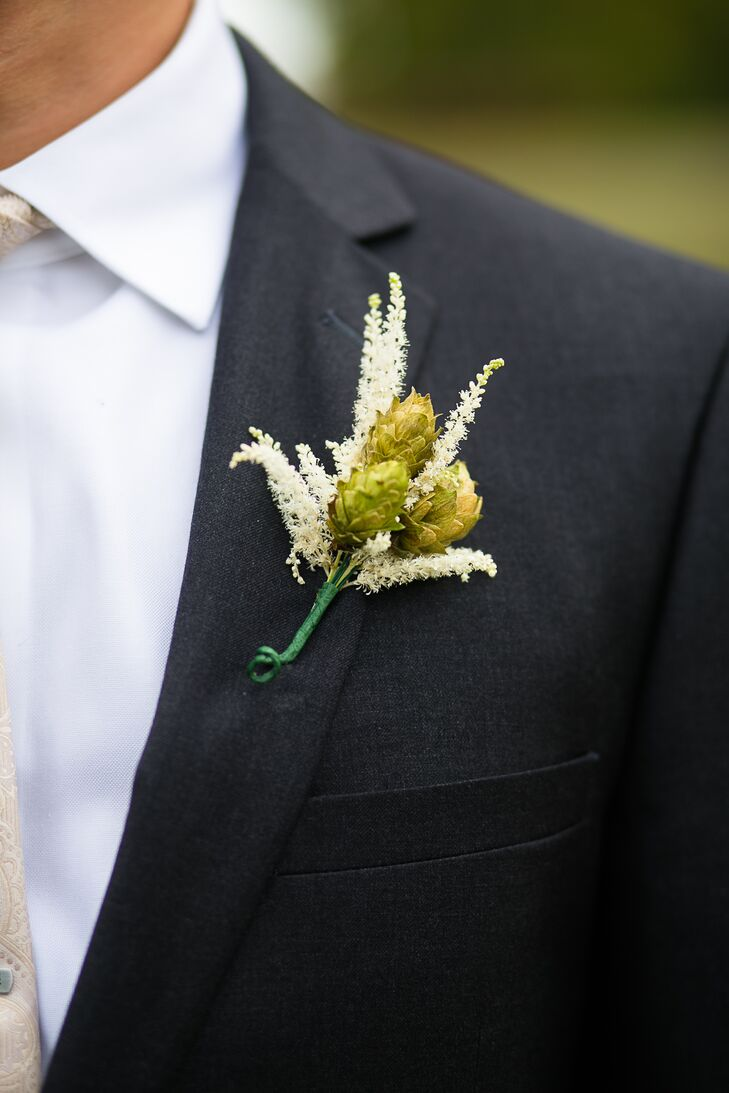 Mike and his groomsmen dressed for the wedding in gray suits paired with white shirts and brown shoes. To complement the farm setting, each man also added a whimsical touch to his attire. All wore fun boutonnieres of green hops surrounded by white astilbes and tied with green ribbon.