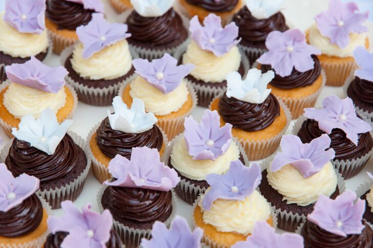 A variety of chocolate and vanilla cupcakes were decorated with purple flower toppers and served to guests as a dessert at the reception.