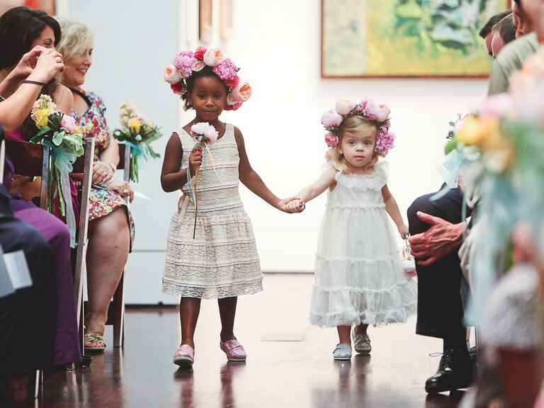 Flower girls walking down the aisle in flower crowns