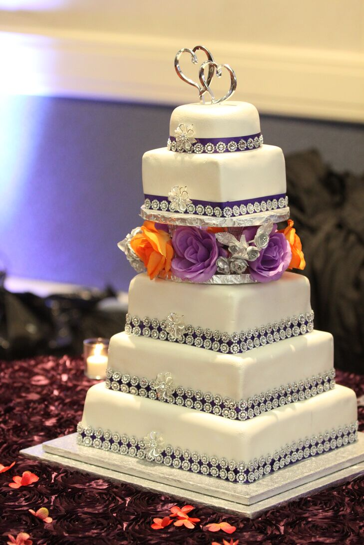Omotayo and Mayowa had an immense six-tier wedding cake trimmed with purple ribbon and rhinestones for sparkle. It was decorated with layer of purple and orange roses and topped with a silver intertwined heart cake topper.