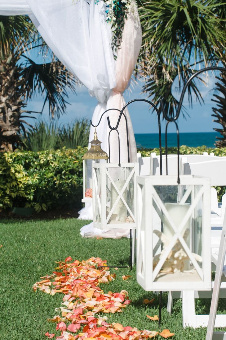 Their aisle decor definitely caught our attention. Channeling the Hammock Beach Resort's ocean view with a nautical touch, they lined the ceremony with bold white lanterns on shepherd's hooks. Sand and seashells filled each one alongside a large white candle.