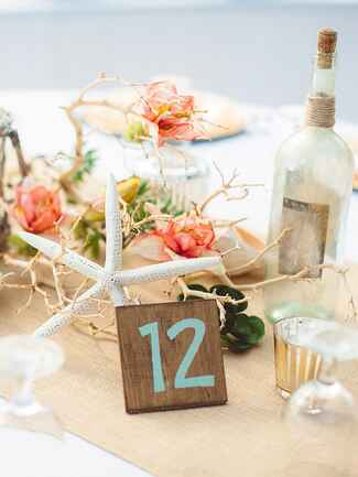 Nautical reception table decor with coral, a starfish and empty bottle