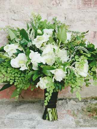 A bridal bouquet with ivory roses and white anemones
