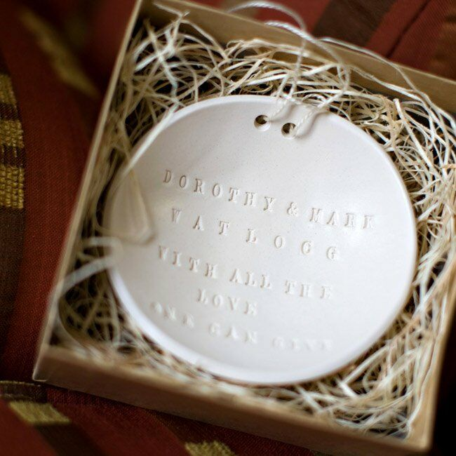 "The couple carried their rings in a two-sided ""bowl"" with a personal message. If you're thinking of stealing this idea, there's an added bonus: You can reuse it as a change tray or candy dish after the wedding."