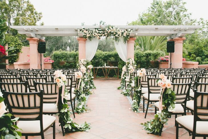 Greenery and peach and white blossoms decorated the aisle and the pergola that Carly and Kevin said their vows under.