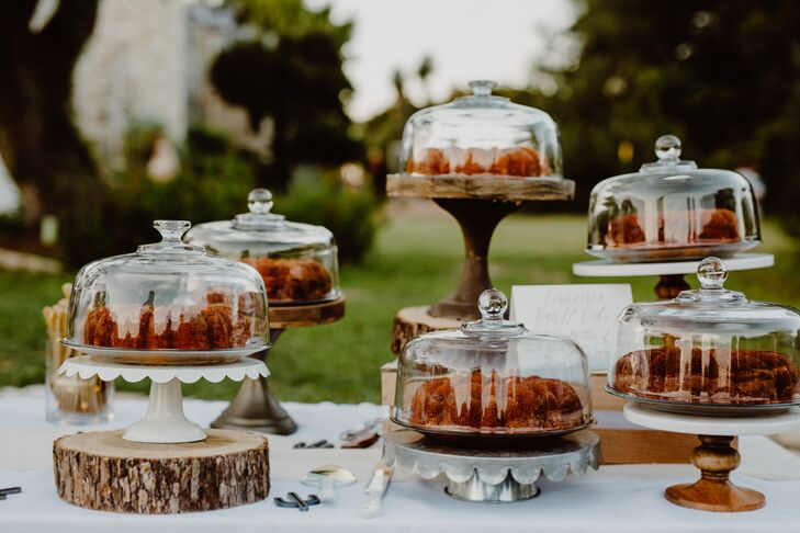 After dinner, guests cut into one of several cakes made by Emily. Wooden slab platters and vintage cake stands added to the eclectic display.