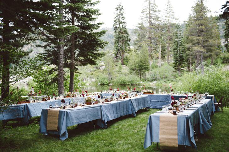 The reception took place outside on their family friend's property in Alpine Meadows, California. Dining tables were dressed in slate blue tablecloths and draped with burlap runners that hung over the edges.