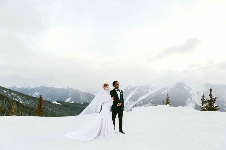 Couple surrounded by snowy mountains at their winter wedding