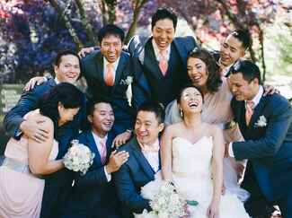 Mismatched wedding party with more groomsmen than bridesmaids laughing together with the bride and groom.