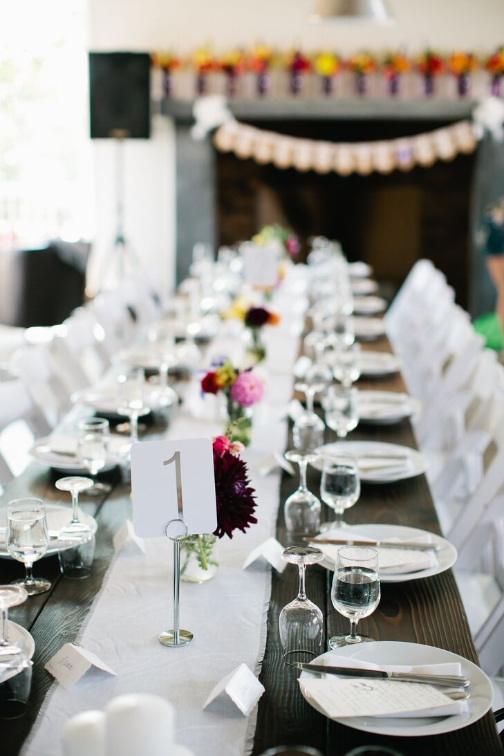 The indoor reception space had long wood tables with white table runners, decorated in the middle with colorful small flower arrangements. Table numbers marking where guests sit were on simple, white stationary.
