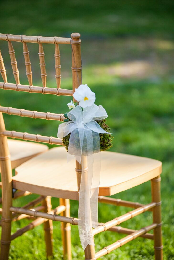 The ceremony  aisles were marked by pockets of moss with white flowers and organdy ribbon.