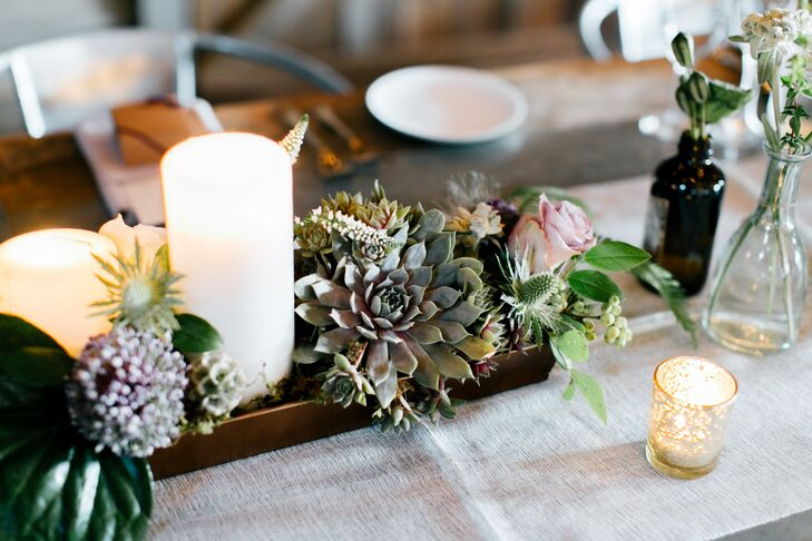 While no two centerpieces were alike, each featured low arrangements of flowers, small florals in apothecary bottles, troughs of herbs, mercury glass candle holders, lanterns and pillar candles.
