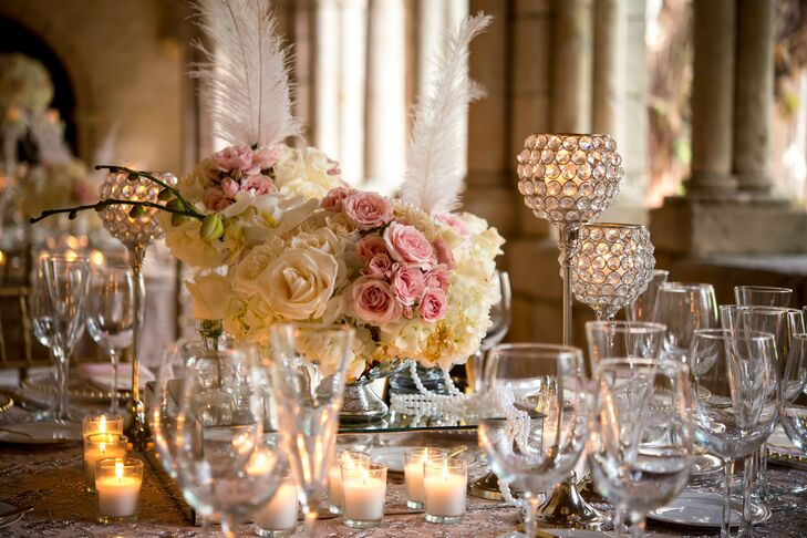 Jacqueline wanted to create her reception dining tables using mismatched elements that all followed the elegant, glamorous style. Table linens were in various patterns and textures, while centerpieces included blush and white bouquets with pearls, candles and feathers.