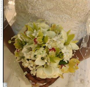 The bride carried a bouquet of micro calla lilies, green micro and gold cymbidium orchids, white ranunculuses, green hypericum berries, and white stephanotis with crystal centers; her maids held smaller versions with the stems wrapped in gold ribbon with long trailing ends.