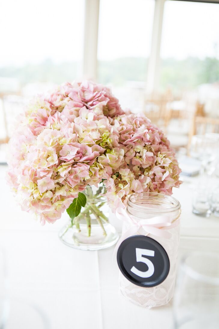 """I wanted a soft color scheme inside to go with the mountain view,"" Kelley says. Each table was paired with a low arrangement of pink and green hydrangeas, which ensured that it wouldn't obstruct their guests' views. The table numbers were placed nearby on clear glass jars wrapped in light pink lace."